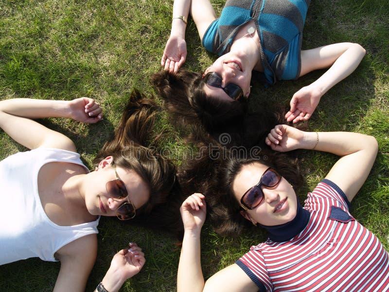 Filles s'étendant sur l'herbe photos stock