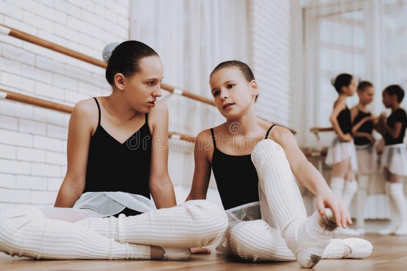 Filles se reposant après la formation de ballet sur le plancher photographie stock