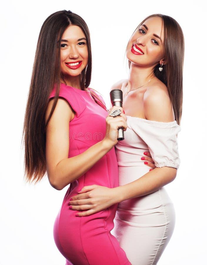Filles sensuelles chantant avec le microphone image stock