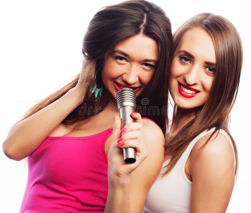 Filles sensuelles chantant avec le microphone images stock
