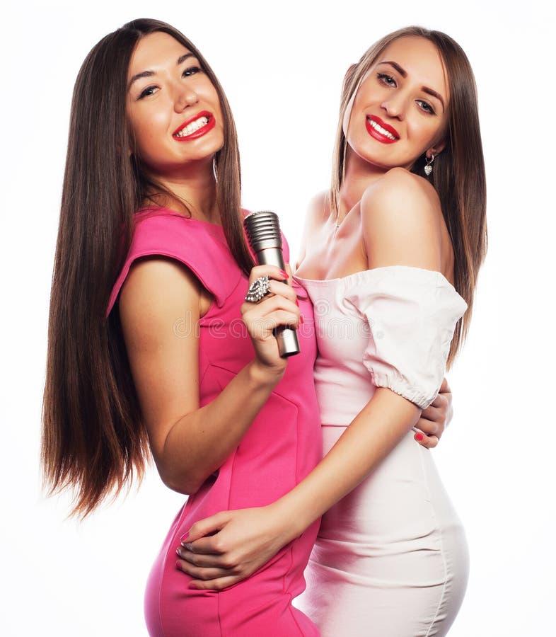 Filles sensuelles chantant avec le microphone photo stock