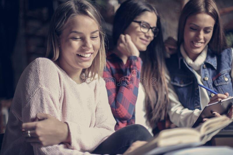 Filles souriantes d'étudiants apprenant ensemble photo stock