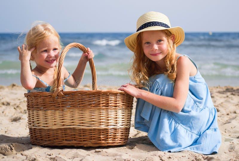 Filles sur la plage avec un panier photo stock