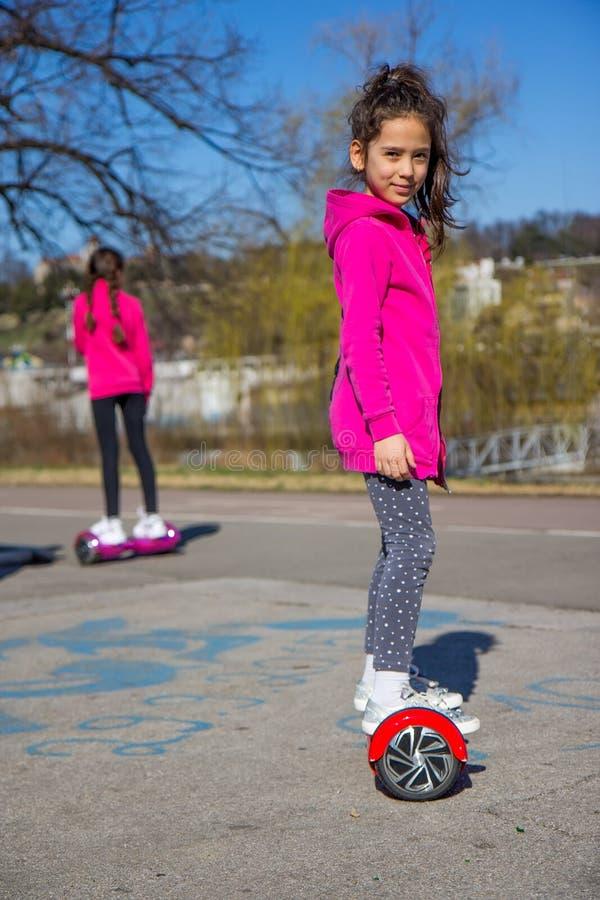 Filles sur le hoverboard photographie stock libre de droits