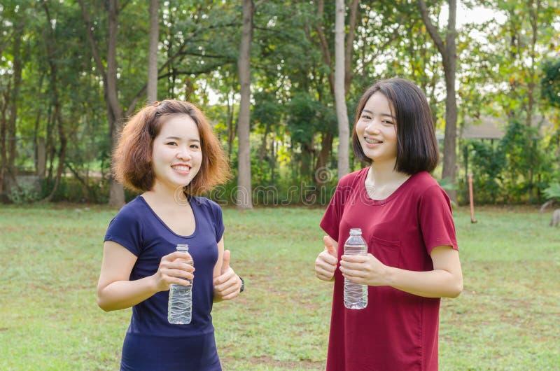 Filles tenant la bouteille d'eau et montrant le pouce  photos stock