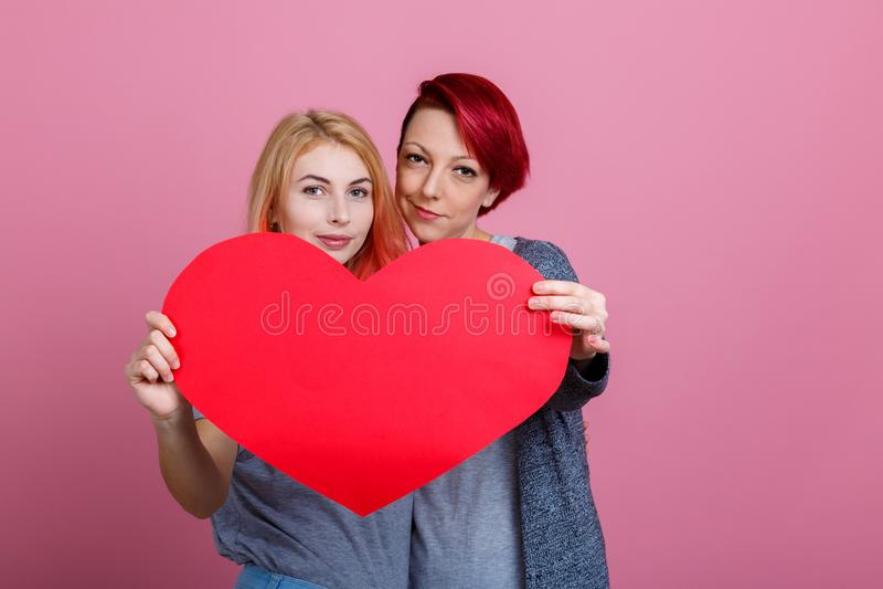 Filles tenant un coeur sur les mains tendues sur un fond rose photo stock