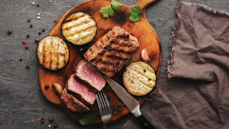 Fillet of beef steak medium rare with vegetables and spices sliced on a cutting board.View from above royalty free stock photography