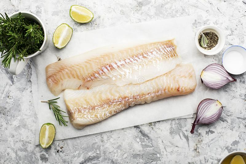 Fillet of fresh raw sea cod on a sheet of parchment on a simple light background with sea salt, ground pepper, sweet. Onion rosemary and lime slices before royalty free stock photo