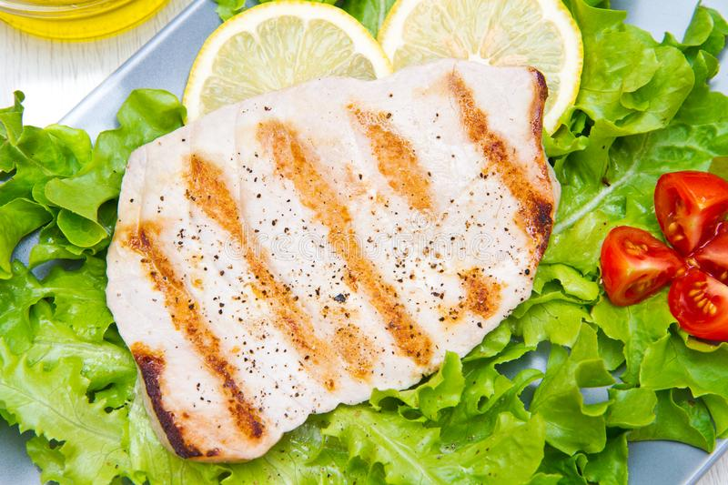 Fillet of grilled tuna with salad and tomatoes. A fillet of grilled tuna with salad and tomatoes stock photography