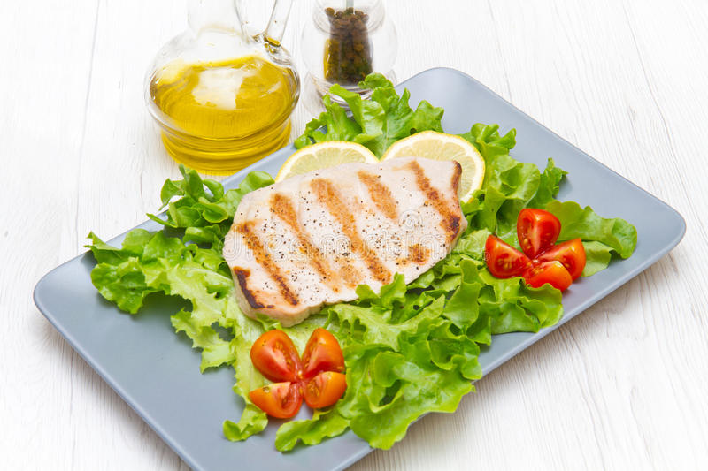 Fillet of grilled tuna with salad and tomatoes. A fillet of grilled tuna with salad and tomatoes royalty free stock images