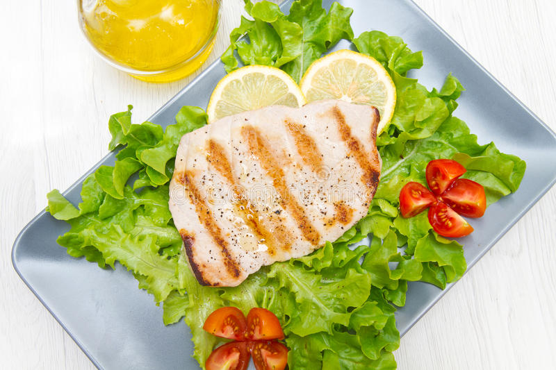 Fillet of grilled tuna with salad and tomatoes. A fillet of grilled tuna with salad and tomatoes royalty free stock photo