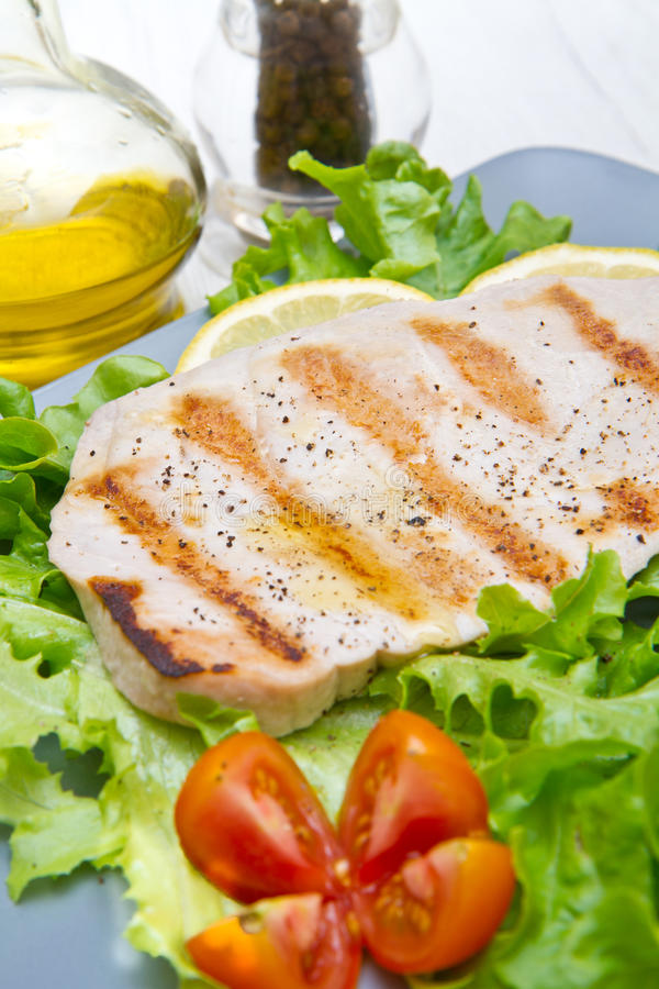 Fillet of grilled tuna with salad and tomatoes. A fillet of grilled tuna with salad and tomatoes royalty free stock image