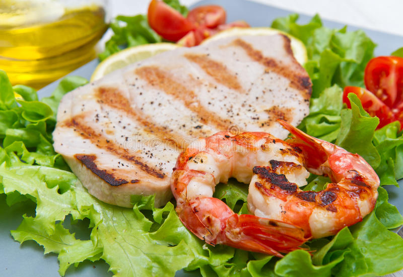Fillet of grilled tuna with salad and tomatoes. A fillet of grilled tuna with salad and tomatoes stock photo