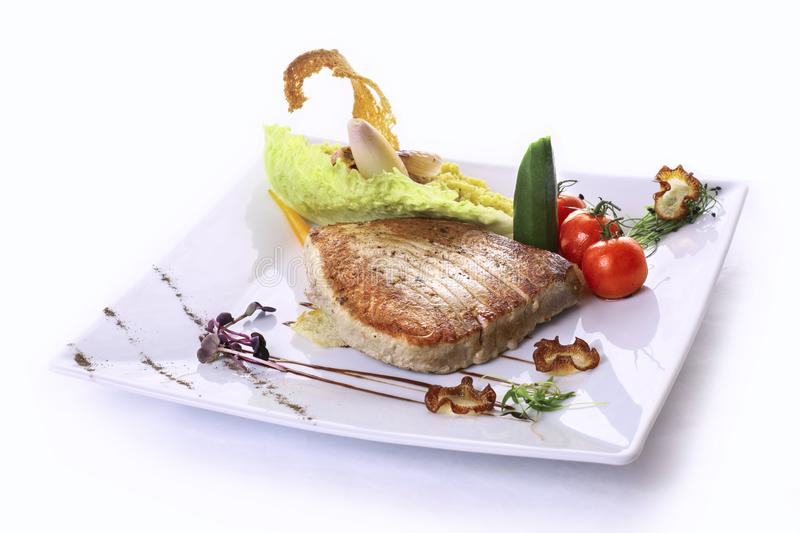 Fillet of grilled tuna. With stewed tomatoes and onion chop BIO couscous stock photo