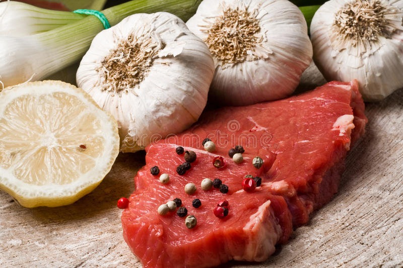 Fillet Mignon. On wood with pepper and garlic stock photo