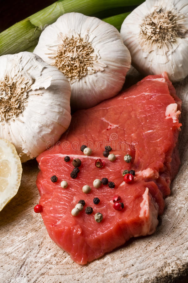 Fillet Mignon. On wood with pepper and garlic royalty free stock photo