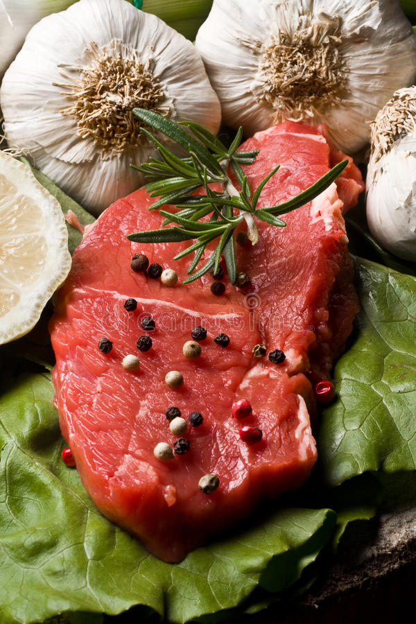 Fillet Mignon. On wood with pepper and garlic royalty free stock image