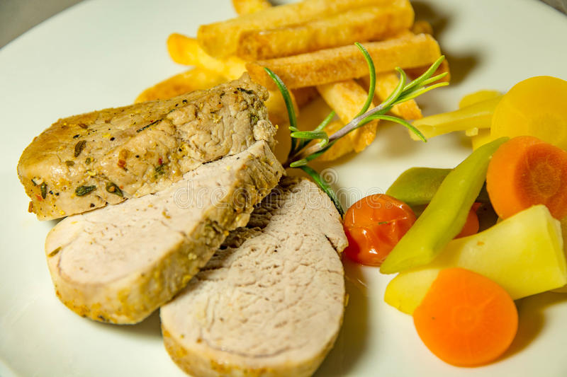 Fillet mignon of pork. With french fries and vegetables stock photo