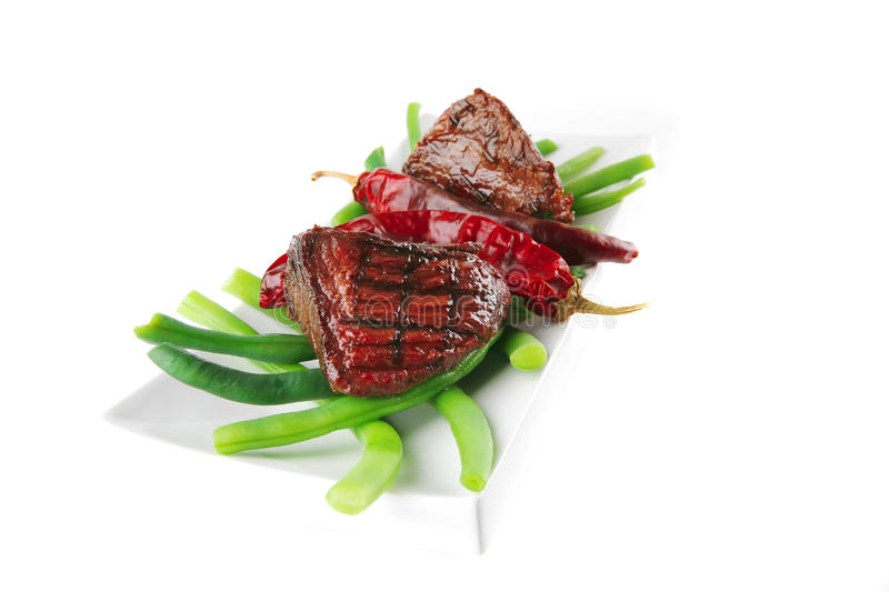 Fillet mignon on a white plate. Fillet mignon served on a white plate with peppers stock photos