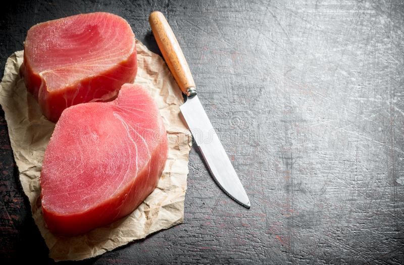 Fillet of raw tuna on the paper with a knife. On dark rustic background royalty free stock image