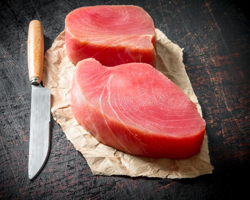 Fillet of raw tuna on the paper with a knife. On dark rustic background royalty free stock images