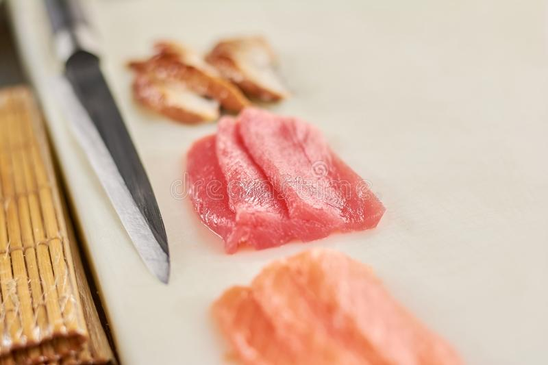 Fillet of raw tuna, salmon and eel. Ingredients for cooking nigiri sushi on white cutting board. Raw fish pieces and knife close up stock image