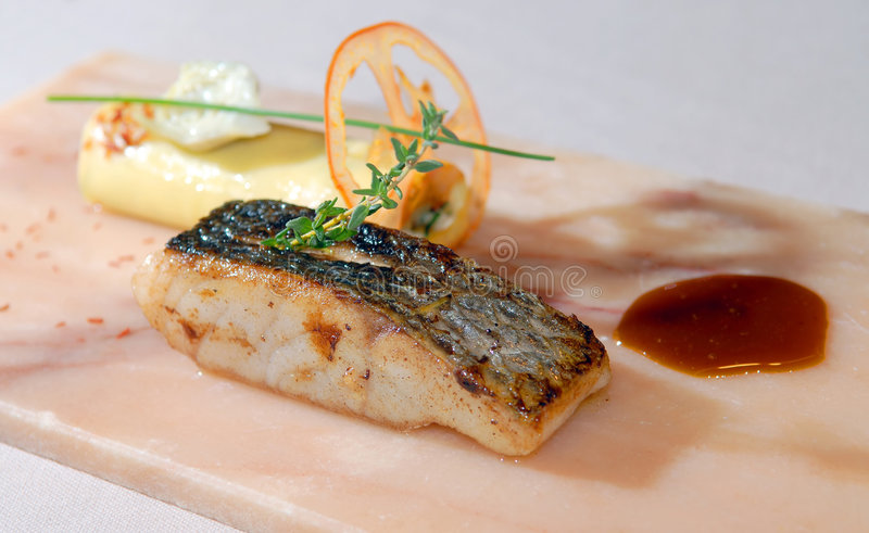 Fillet sea bass and canneloni. With artichokes royalty free stock photography