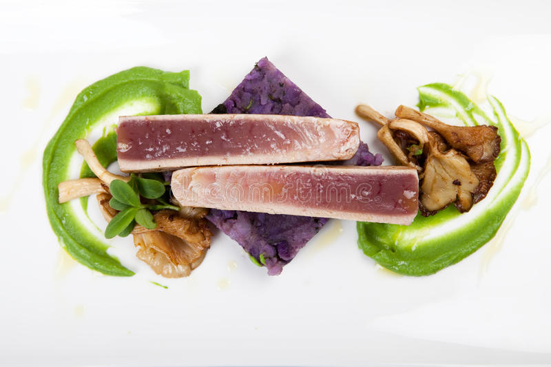 Fillet of tuna with mushroom and potatoes. Seafood dinner with fillet of tuna, mushy peas, potatoes and oyster mushrooms royalty free stock photography