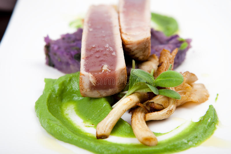 Fillet of tuna with oyster mushrooms, potatoes and pea puree. Fillet of tuna with oyster mushrooms, green pea puree and purple colored potatoes royalty free stock photo