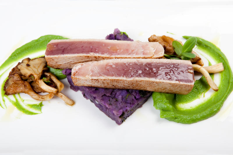 Fillet of tuna with purple potatoes, mushrooms and mushy peas. Fillet of tuna on purlpe colored potatoes, with oyster mushrooms and mushy peas stock photo