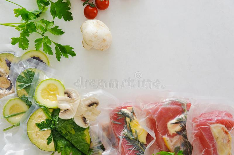 Fillet and vagatables in vacuum bags for sous vide coocing on white marbleized background royalty free stock photography