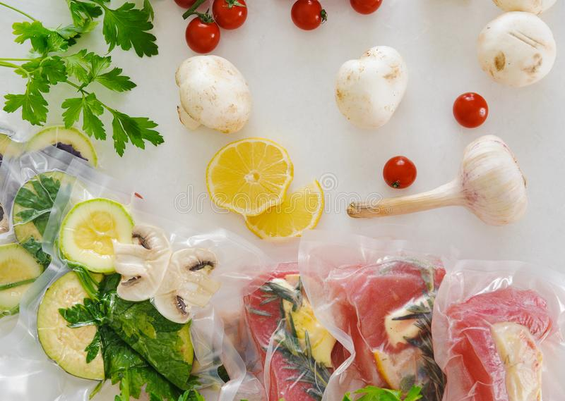 Fillet and vagatables in vacuum bags for sous vide coocing on white marbleized background stock photo