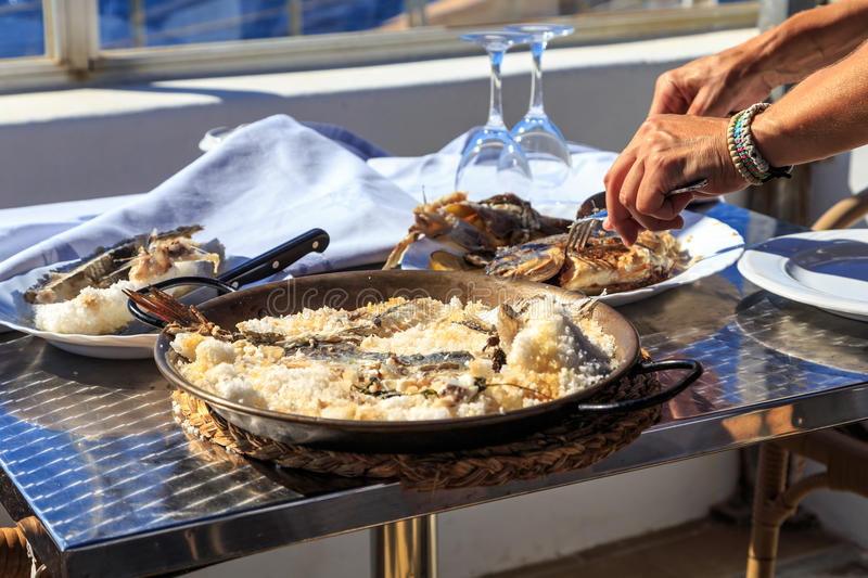 Filleting fish. Waiter filleting salted fish at table side stock photo