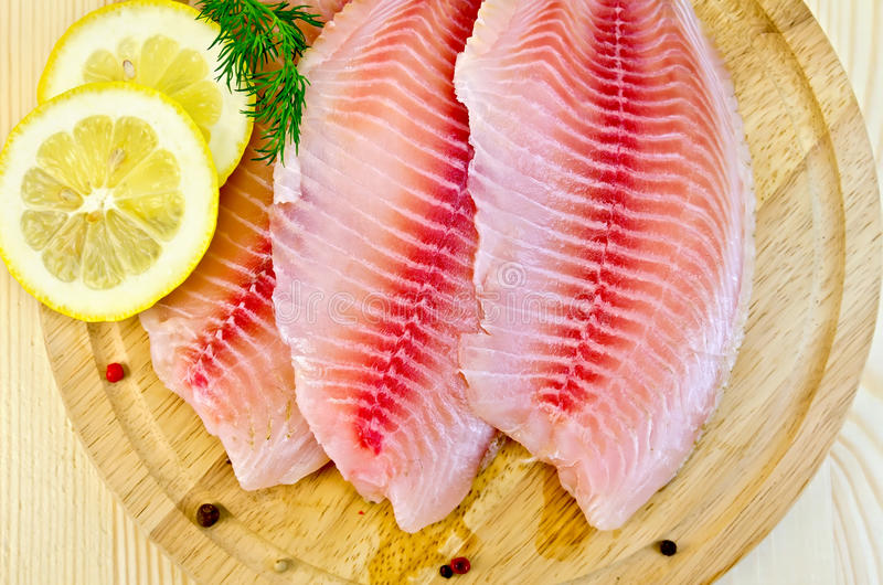 Fillets tilapia with lemon on a round board royalty free stock photos