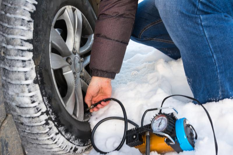 Filling air into a car tire. Winter. Closeup of a repairing a flat tire use compressor stock photography
