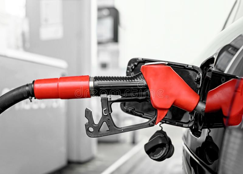 Filling the car with fuel. On petrol station closeup. Red fuel nozzle stock photos