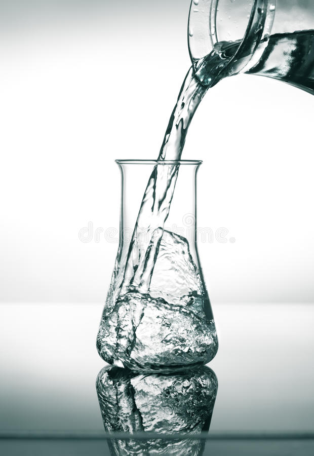 Filling in conical flask with water. Scientific conical flask being filled with water stock image