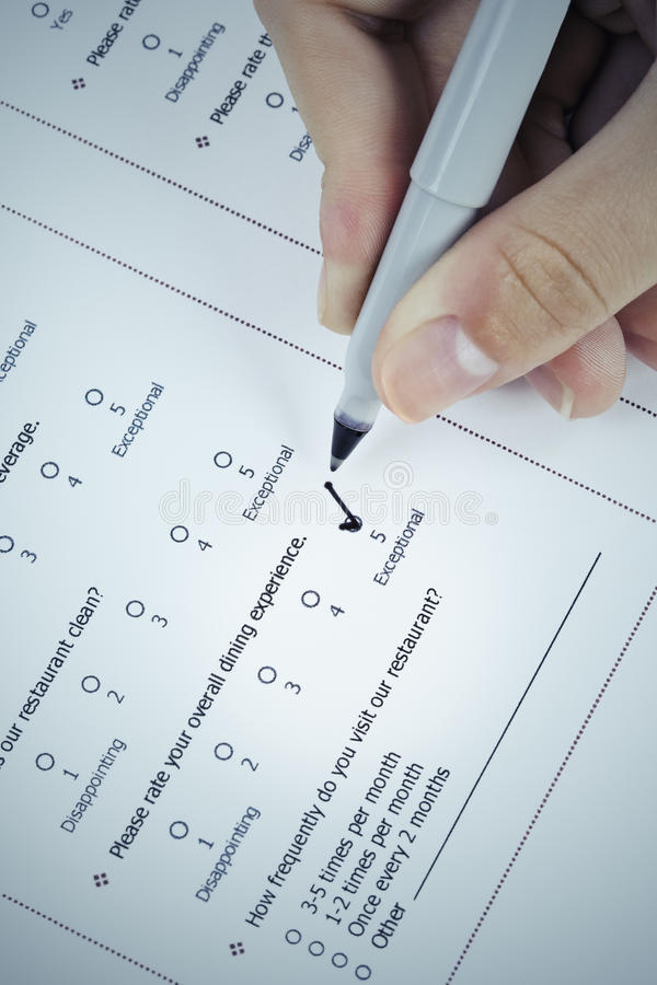 Filling in customer satisfaction survey form stock image