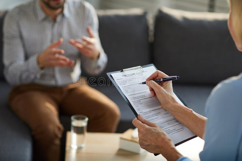 Filling in document. Mature professional counselor filling in document while having discussion with patient in trouble stock image