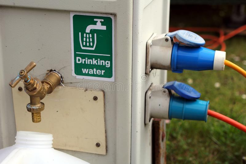 Filling a drinking water container at a campsite water and electricity supply point stock image