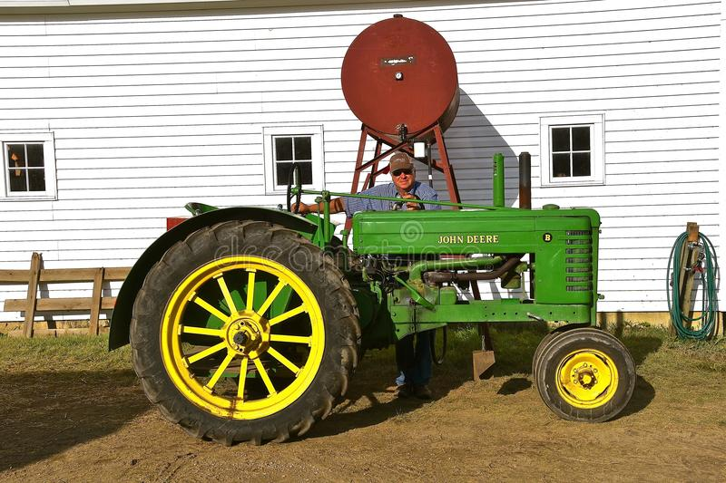 Filling a gas tank on an old John Deere B. ROLLAG, MINNESOTA, Sept 2, 2017: The unidentified operator of an old John Deere B tractor filling gas is occurring at royalty free stock images