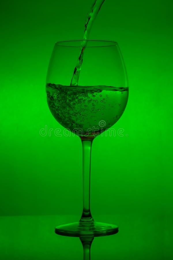 Filling the glass, pouring wineglass on green background royalty free stock photography