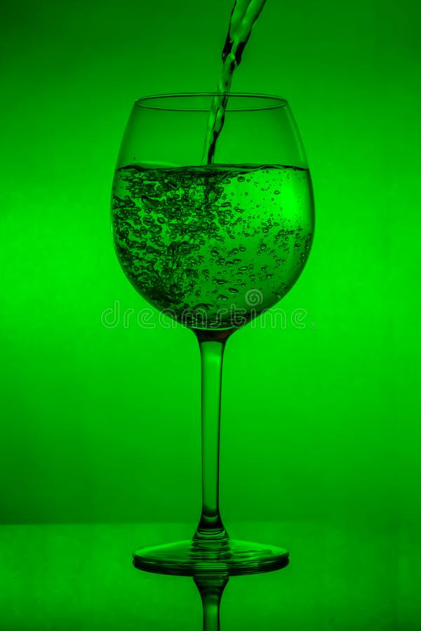 Filling the glass, pouring wineglass on green background stock image