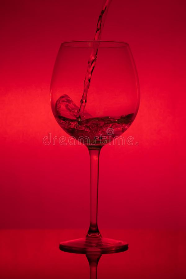 Filling the glass, pouring wineglass on red background stock photography