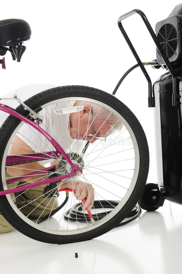 Filling Granddaughter`s Tire. A senior man filling his granddaughter`s bike tire, and aircompressor nearby. On a white background stock photography