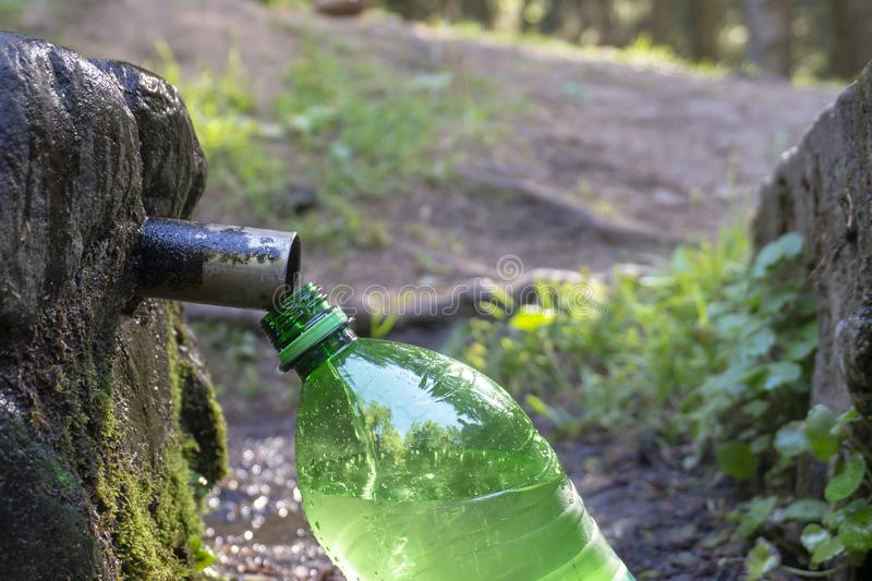 Filling a green plastic water bottle at a fountain stock image