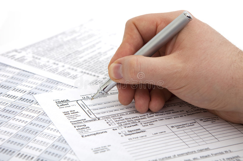Filling income tax form. With pen isolated against white background stock photos