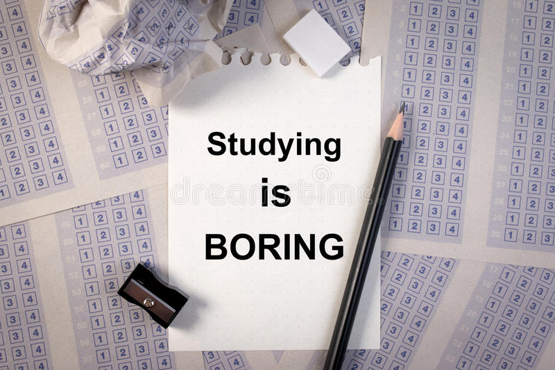 Filling out in answer sheet, pencil, sharpener, paper reduction and the word studying is boring. stock image