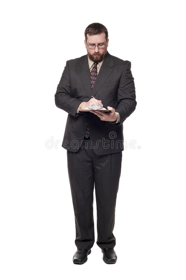 Filling out job application on clipboard. Isolated full length studio shot of the front view of a businessman writing on a clipboard royalty free stock photo