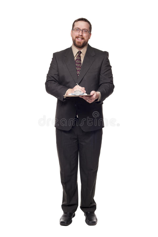 Filling out job application on clipboard fro. Isolated full length studio shot of the front view of a businessman smiling and looking at the camera while writing stock image
